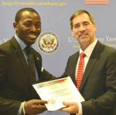 The Programs Manager for InterFaith Vision Foundation Cameroon receives his grant from Ambassador Hoza.